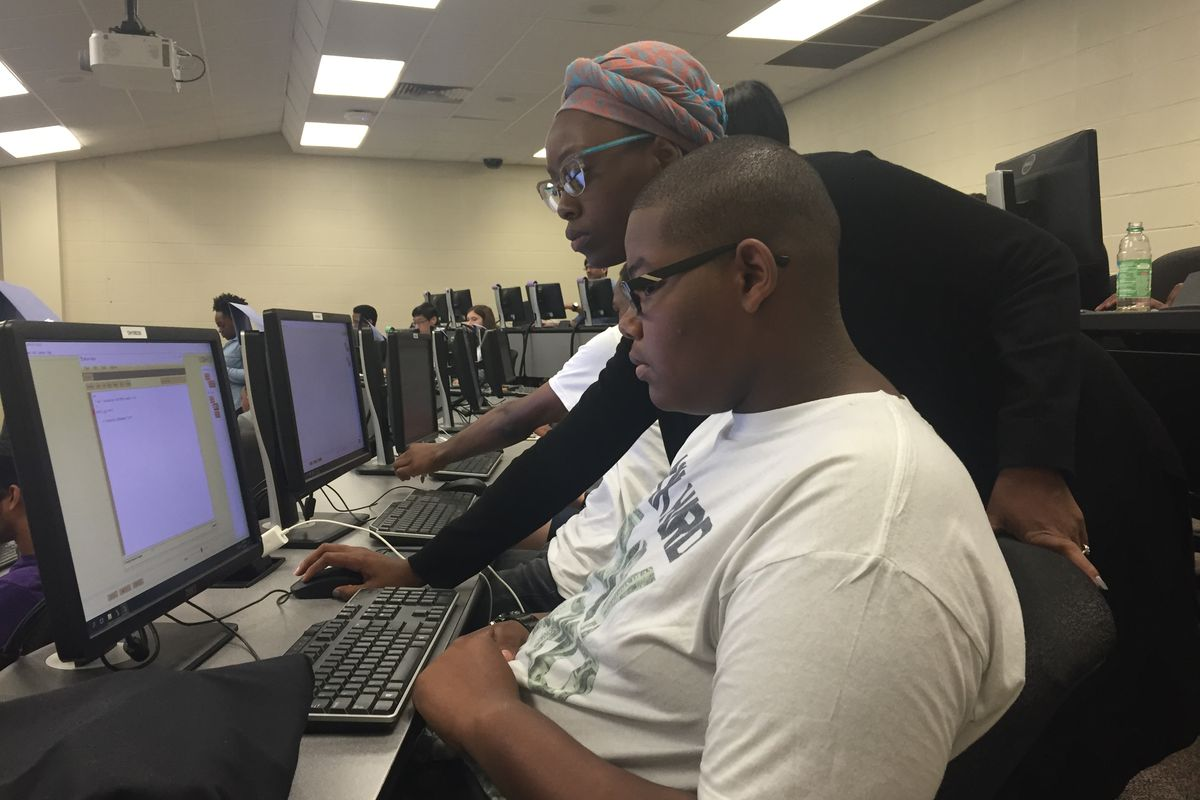 Joshua Williams, a student at Central High School, learns about coding with the help of Terricka Muhammed, a teaching assistant at the University of Memphis.