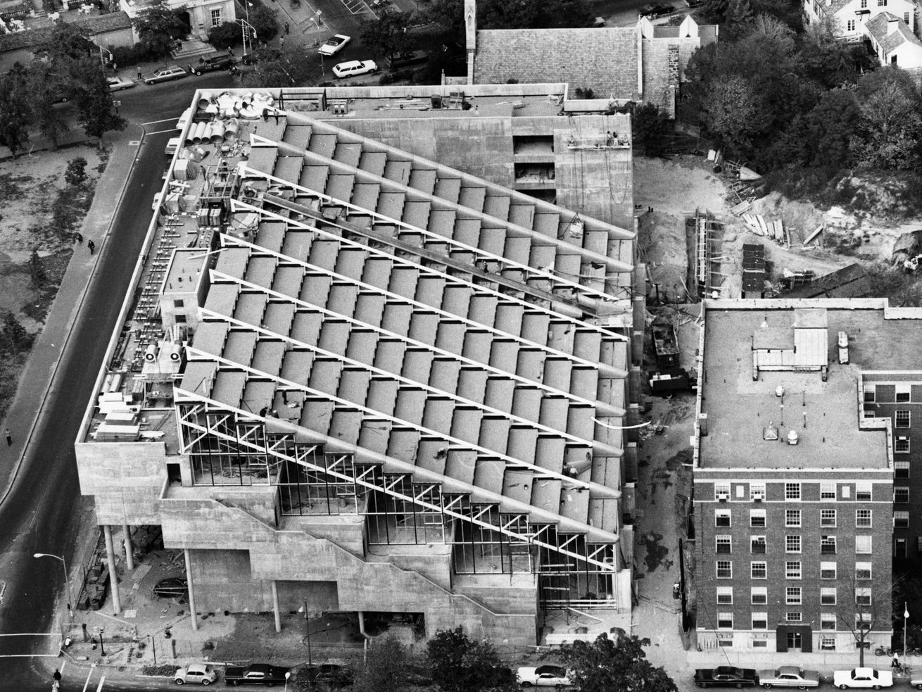 An archival black-and-white aerial photograph of a concrete building with a sloped roof