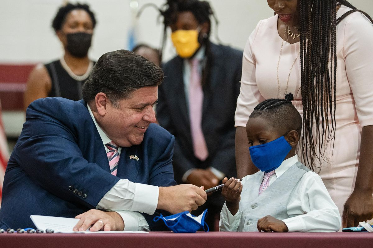 Gov. J.B. Pritzker gives a pen to Jett Hawkins as he signs the Jett Hawkins Act at Uplift Community High School in the Uptown neighborhood on Friday.