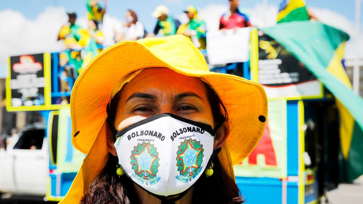 """A woman in a yellow hat wears a face mask that reads """"Bolsonaro."""""""