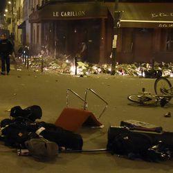 Debris litters the street, candles burn amidst a makeshift memorial