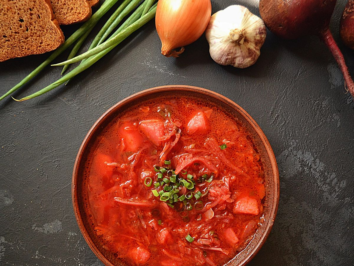 A bowl of borscht and its various ingredients.