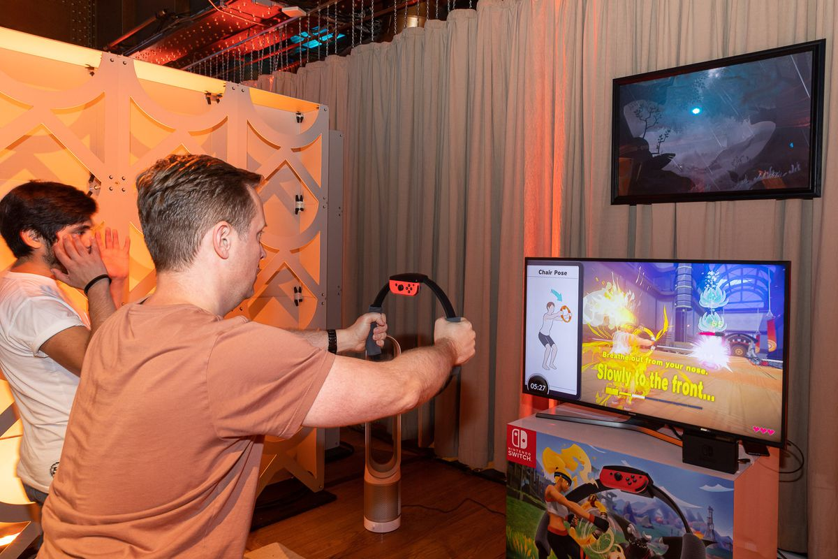 a white man in an orange T-shirt holding the Ring-Con out in front of him while playing Ring Fit Adventure