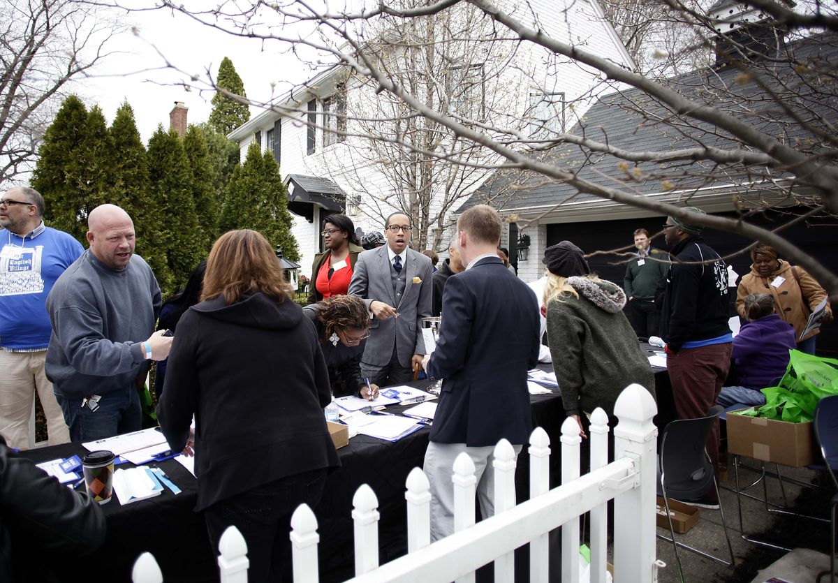 People congregate around a table with flyers outside a house.
