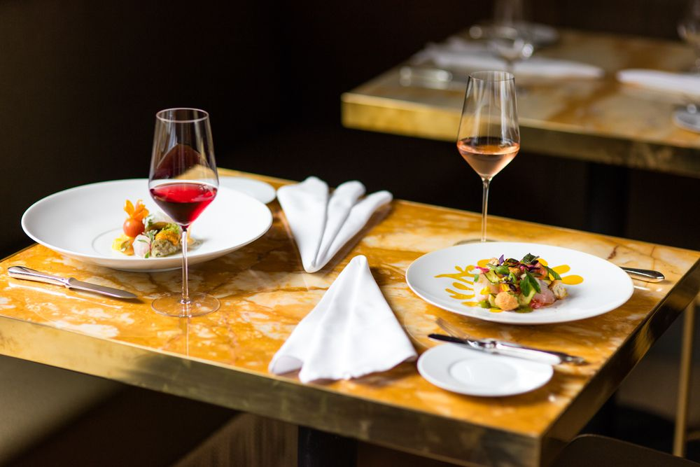 An elegant yellow marble table is set with two dishes of food, two glasses of wine, and two neatly pleated cloth napkins.