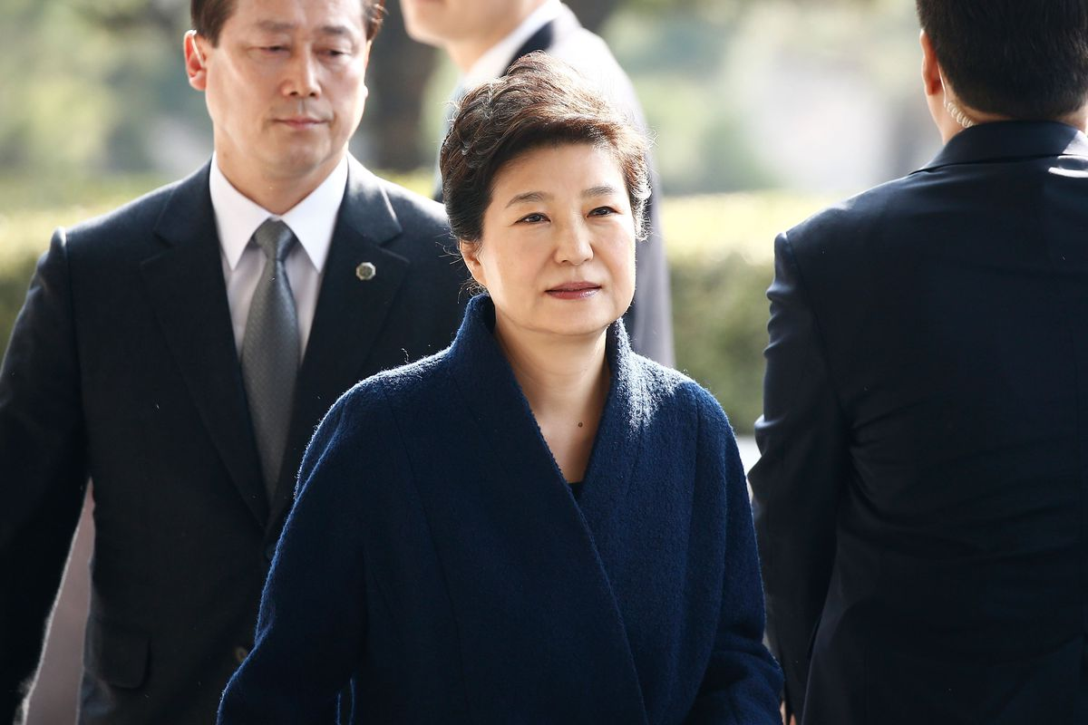 Park Geun-hye stands, wearing a dark blue coat with a man in a black suit standing next to her.