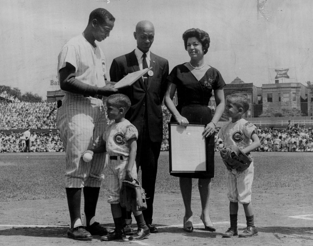 Ernie Banks reads a 1964 proclamation as his father, Edward, wife, Eloyce, and twin sons, Joel and Jerome, listen.   Sun-Times library