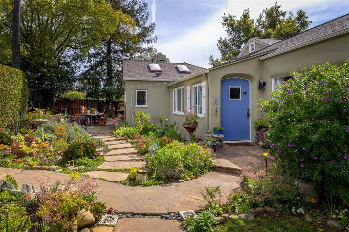 Shot of entrance of simple greyish green home with perwinkle door and lush landscaping.