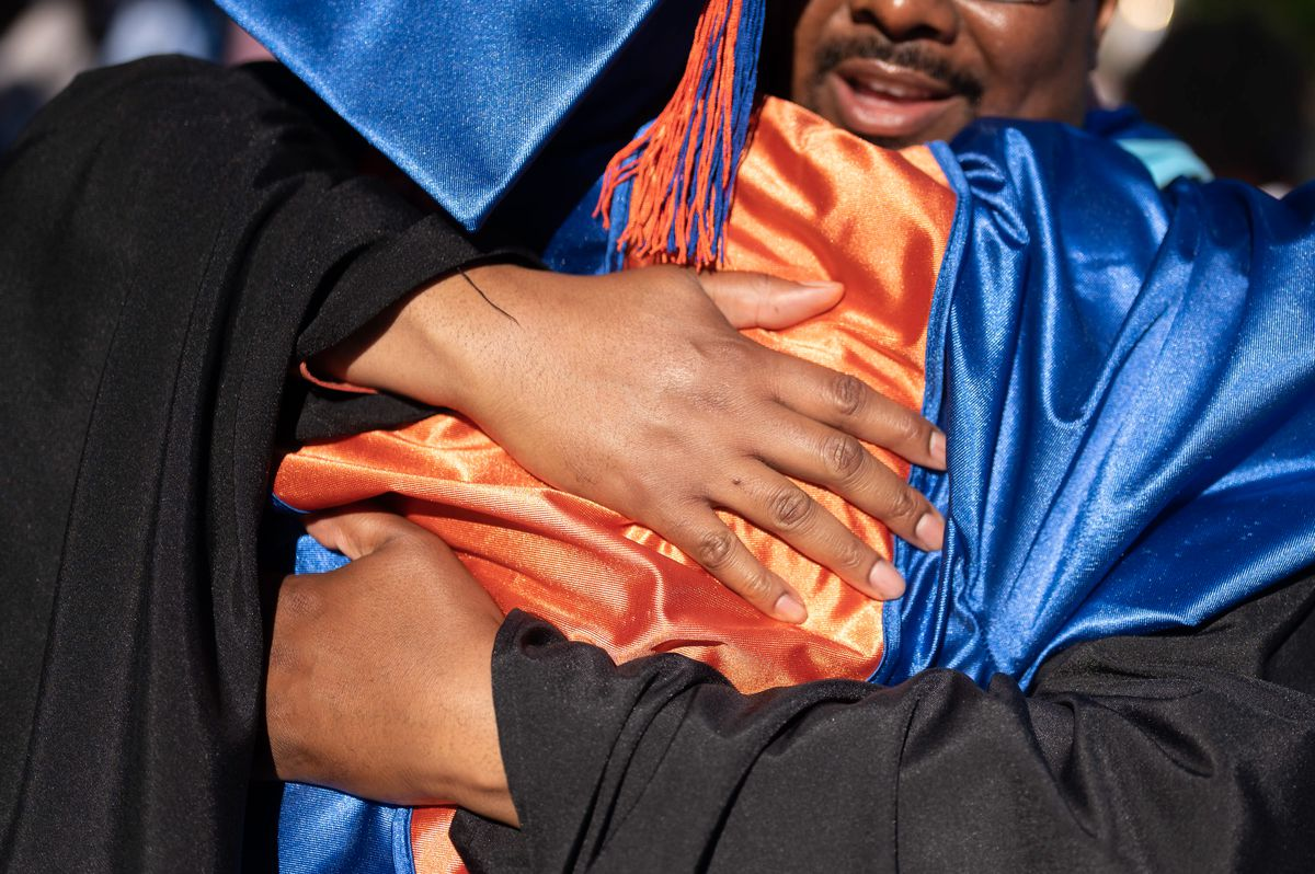 A man wearing black graduation regalia embraces a high school senior wearing a blue and orange cap and gown.