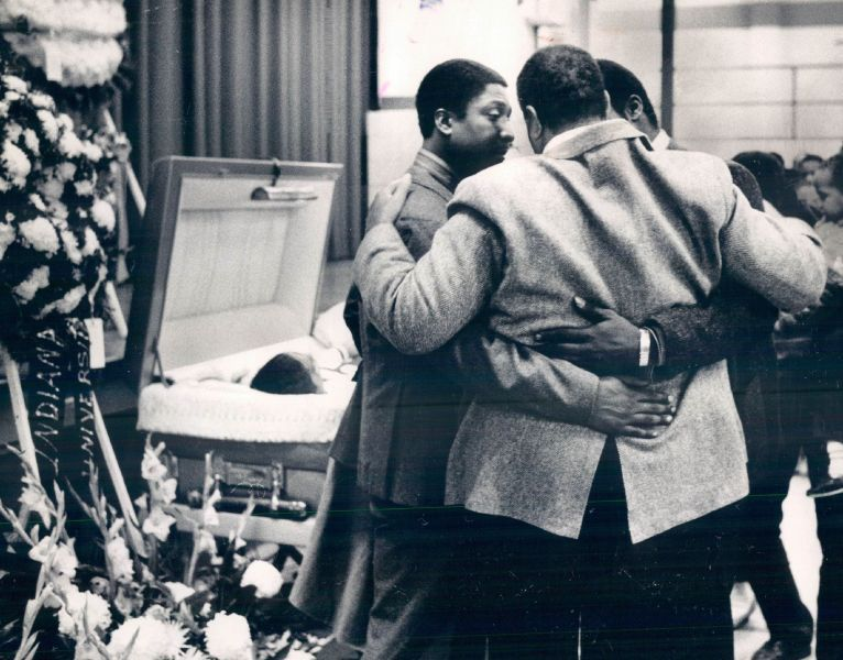 Ben Wilson Sr., father of the slain basketball star, embraces two of his other sons as they arrived at the wake last night at Simeon High School.