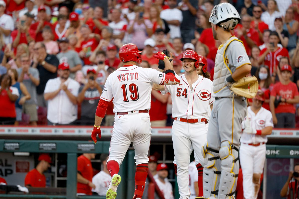 Joey Votto #19 of the Cincinnati Reds is congratulated by Sonny Gray #54 after hitting a three-run home run during the second inning of the game against the Pittsburgh Pirates at Great American Ball Park on August 5, 2021 in Cincinnati, Ohio.