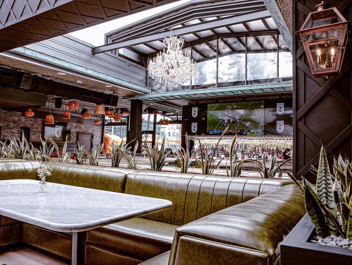 The interior of a bar with a retractable roof, sports on a TV and succulent plants lining the booths