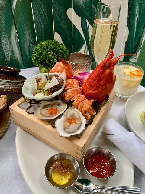 A brown tray composed of seafood dishes including an orange lobster claw