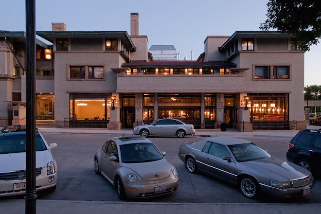 The Park Inn Hotel by Frank Lloyd Wright. The facade is tan and there are multiple windows. There is a street in front of the hotel with cars.