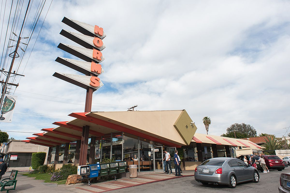 The famous googie diner Norms shown from the outside as cars pull into the parking lot.