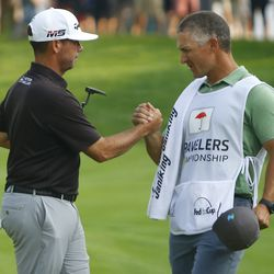 Chez Reavie celebrates with his caddie after making a birdie on the 18th hole in the 2019 Travelers Championship Third Round at the TPC River Highlands in Cromwell, CT on June 22, 2019.