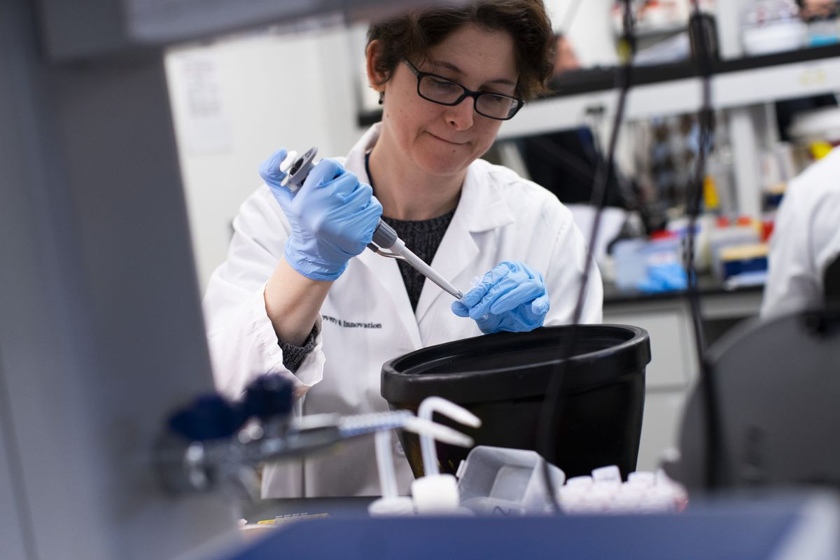 A woman in a lab coat pipettes a liquid into a small vial.