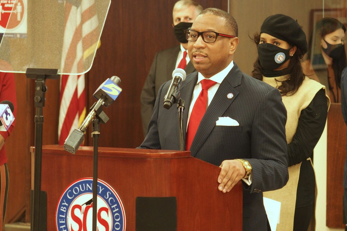 Superintendent Joris Ray stands at a podium with microphones during a press conference as school board chairwoman Miska Clay Bibbs, wearing a mask, looks on from behind.