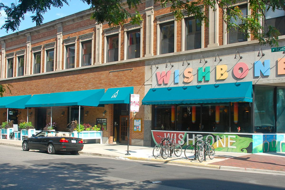 """The outside of a restaurant from the street. A colorful sign reads """"Wishbone"""" over teal awning."""