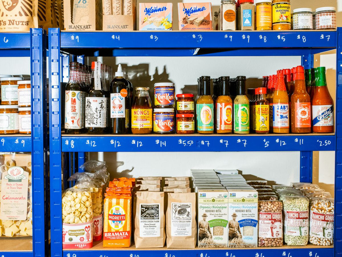 Shelves at Blotto in Seattle stocked with a variety of sauces, grains, baking products, and other pantry items.