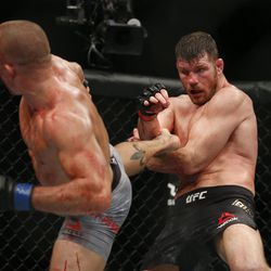 A bloodied St-Pierre throws a kick at the midsection of a similarly bloodied Bisping.