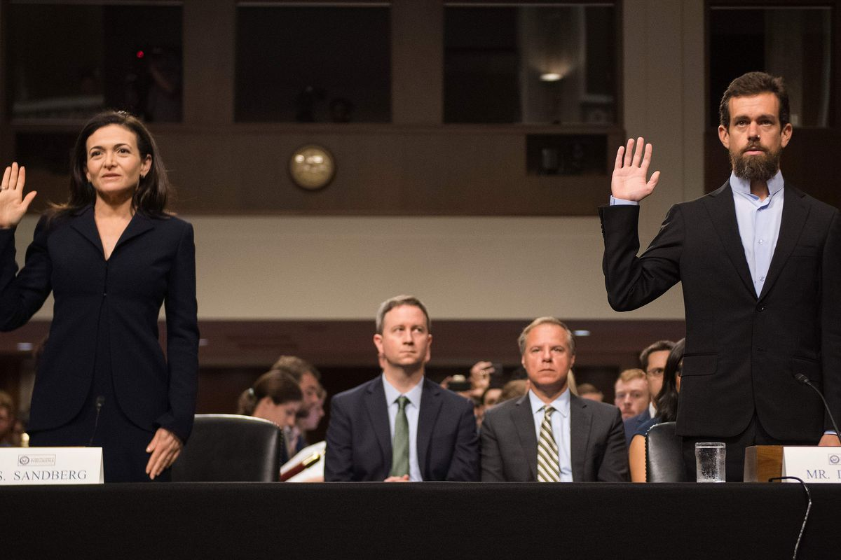 Facebook COO Sheryl Sandberg and Twitter CEO Jack Dorsey hold up their right hands to be sworn in to testify before the Senate Intelligence Committee.