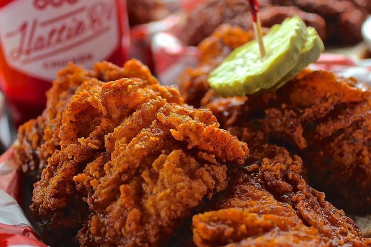 A close up of crispy fried Nashville-style hot chicken, complete with slices of pickle and a toothpick.