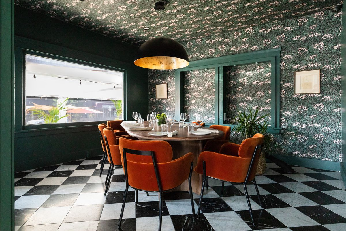 A deep green floral room with orange tufted chairs inside of a restaurant.
