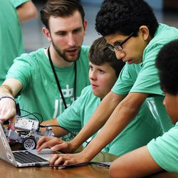 Teacher Aaron Roth, left, of West Jordan Middle School helps students Kirby Horrocks, Roberto Lugo, and Shelby Tolbert prepare their robot for competition as middle school students who have been involved in an after-school STEM program compete in West Jordan on Wednesday, May 27, 2015.