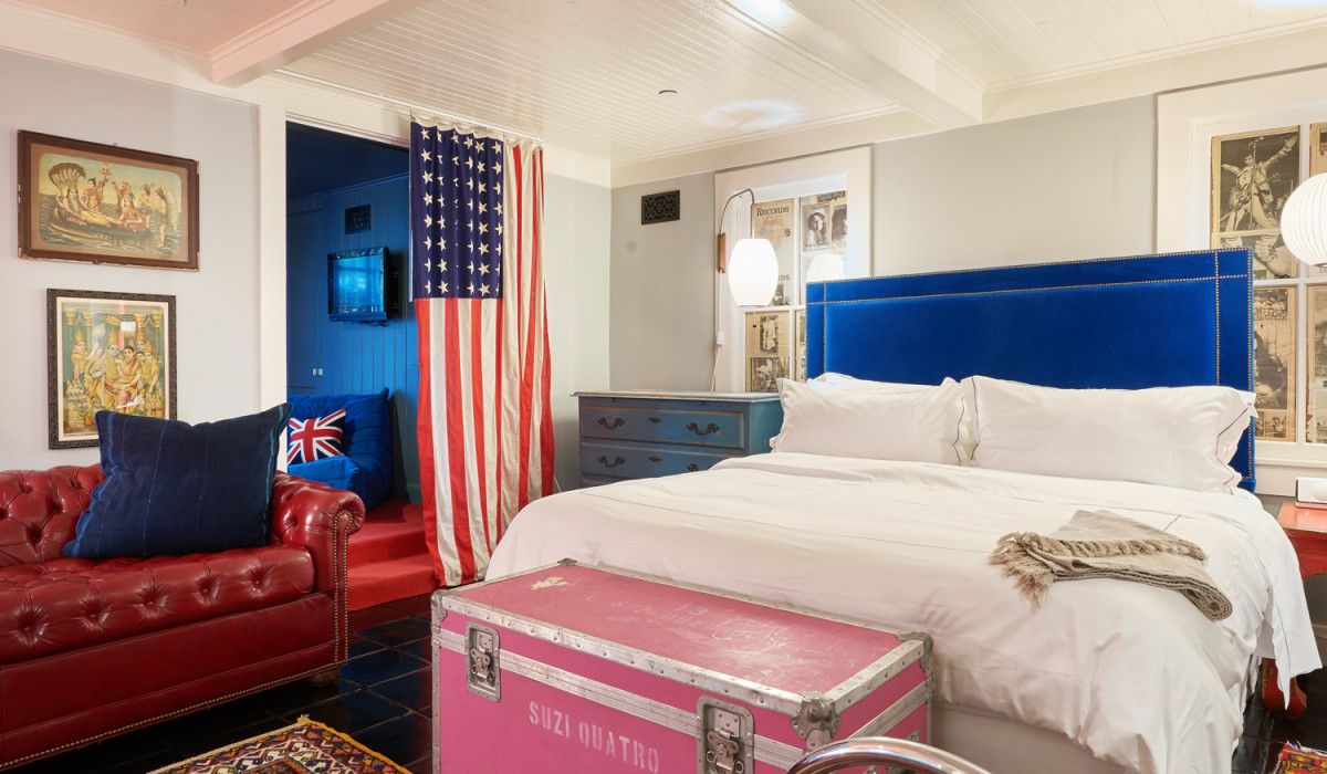 A bedroom in Hotel Saint Cecilia. There is a bed, a pink trunk, a red couch, and a United States flag hanging from the ceiling.