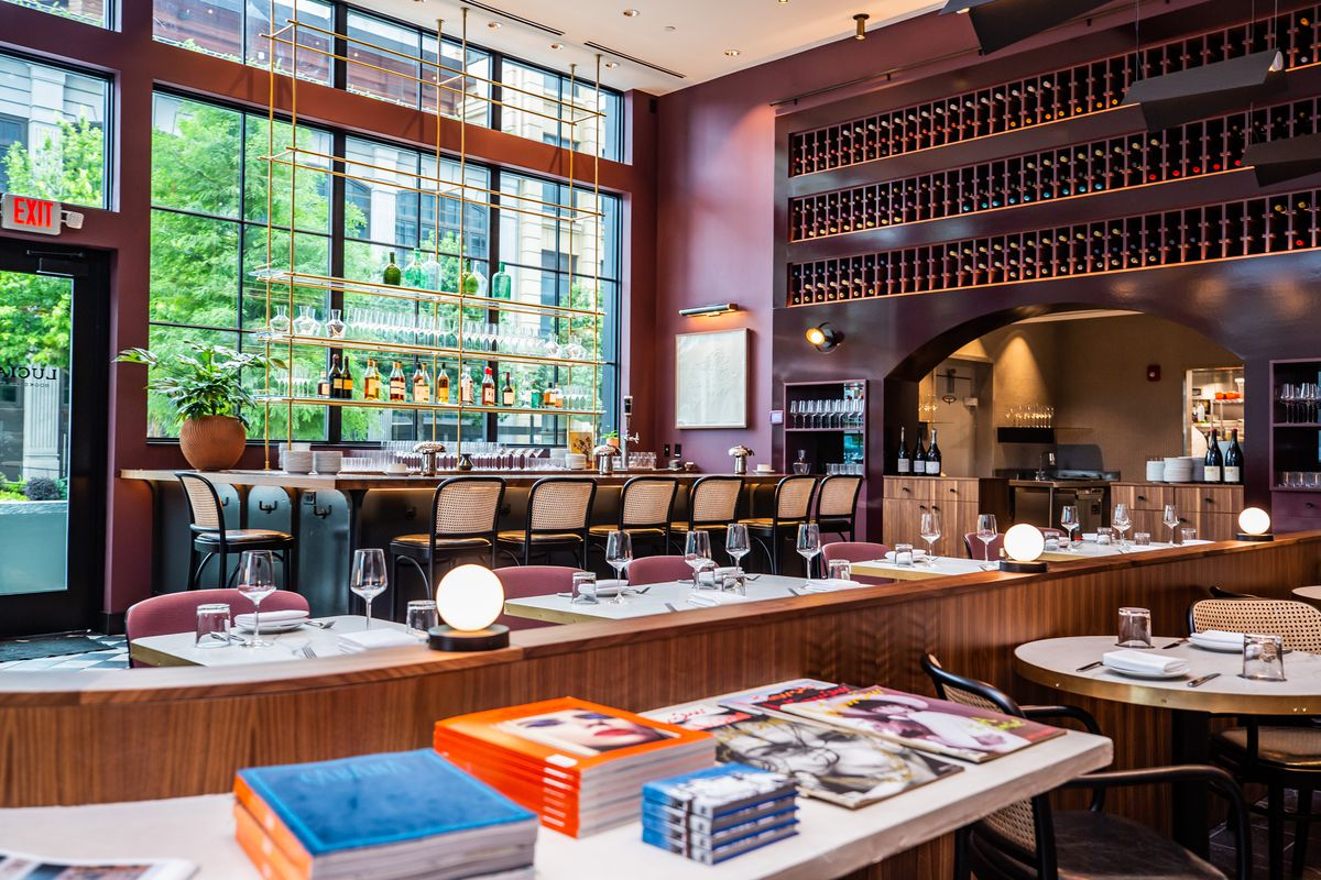 Over looking the the dining room at Lucian in Atlanta with books laid out in stacks neatly on a white counter in the foreground with the bar and its large bank of windows in the background