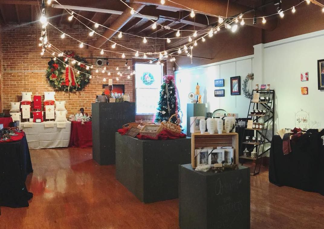 Gallery decorated for Christmas with products displayed on tables.
