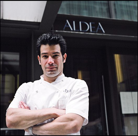 """George Mendes dressed in a chef's coat outside a restaurant with the name """"Aldea"""" written above the door"""