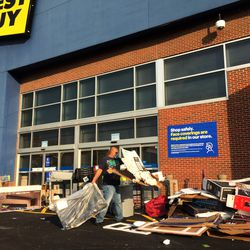 Crews clean up outside the Best Buy store near Marcey and Halsted streets on the Near North Side. Much of the parking lot was strewn with empty flat-screen TV boxes and shredded foam packaging.