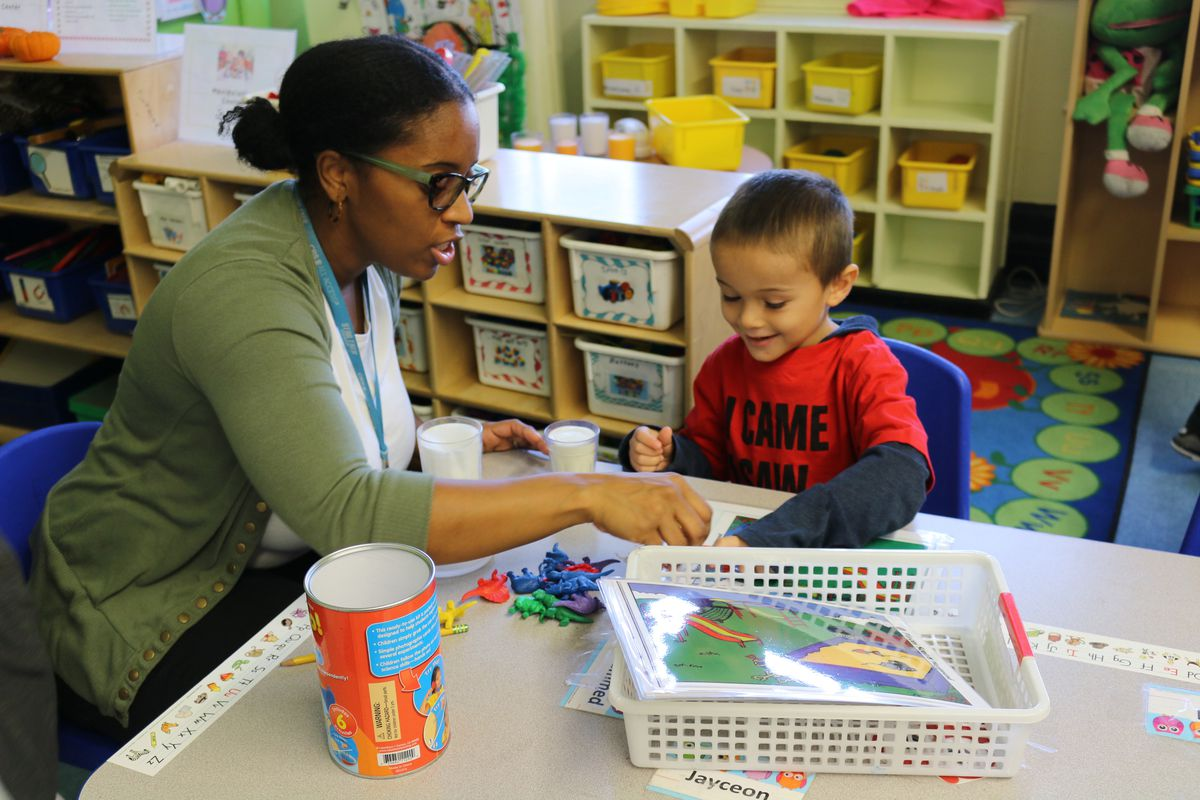 Heather Fontaine, a pre-K teacher at P.S. 277 in the Bronx, counts dinosaur toys with a student during center time.