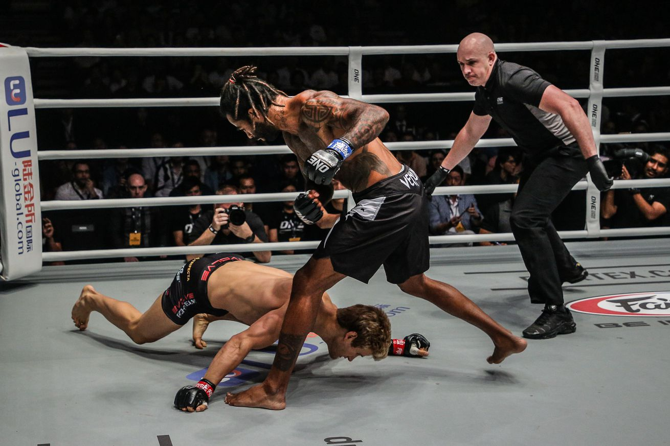 Cosmo Alexandre (blue gloves) stands over a fallen Sage Northcutt (red gloves) at ONE Championship: Enter the Dragon in Kallang, Singapore on May 17