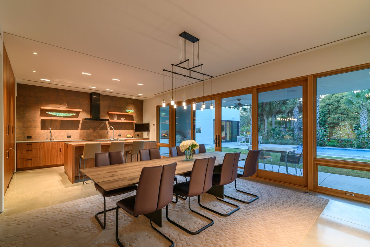 An open-concept kitchen and dining room with a wooden table, eight chairs, and views out to the pool.
