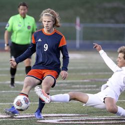 Ridgeline's Jackson Hulse dives in for a kick in front of Mountain Crest's Oliver Thompson during the 4A boys soccer semifinals at Jordan High School in Sandy on Monday, May 17, 2021. Ridgeline won 1-0.