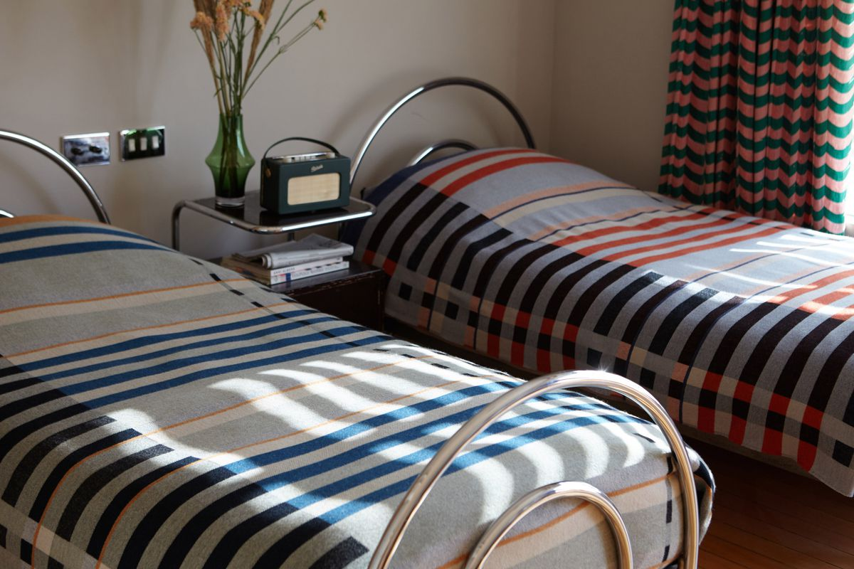 Two beds that have different striped blankets on them.