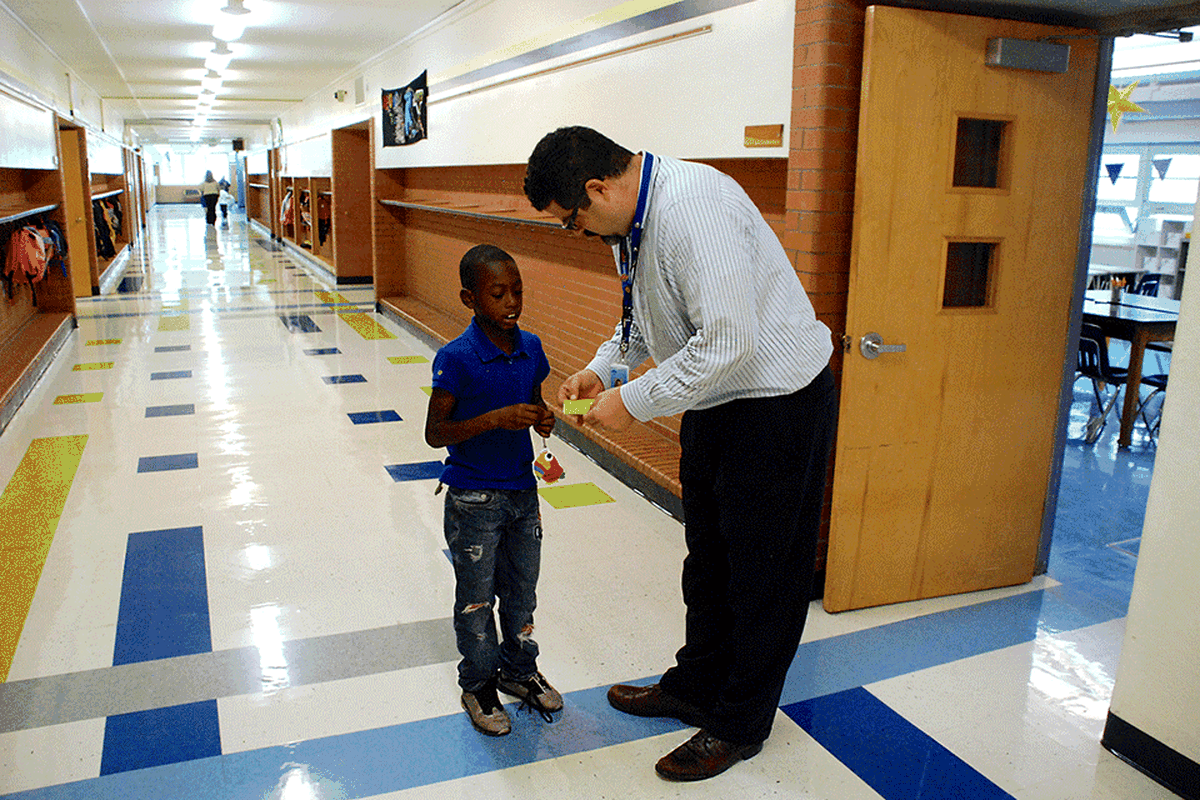 Columbine Elementary School principal Jason Krause looks at a student's hall pass. Krause is Columbine's latest principal, the school's fifth in seven years.