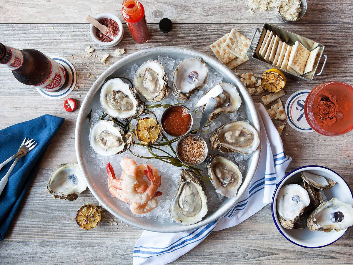 A circular tray of halved oysters and a pile of pink shrimp and ice surrounded by a little bowl with empty oysters shells, condiments, and crackers.