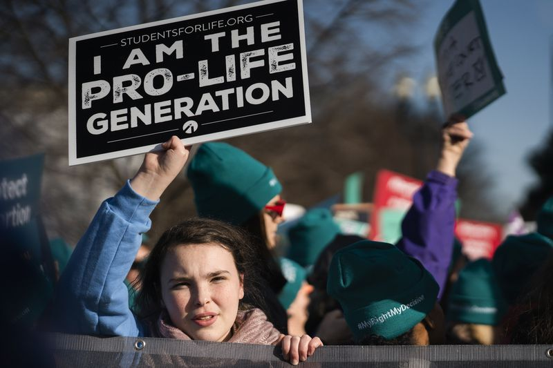 "An anti-abortion demonstrator holds a sign reading, ""I am the pro-life generation."""