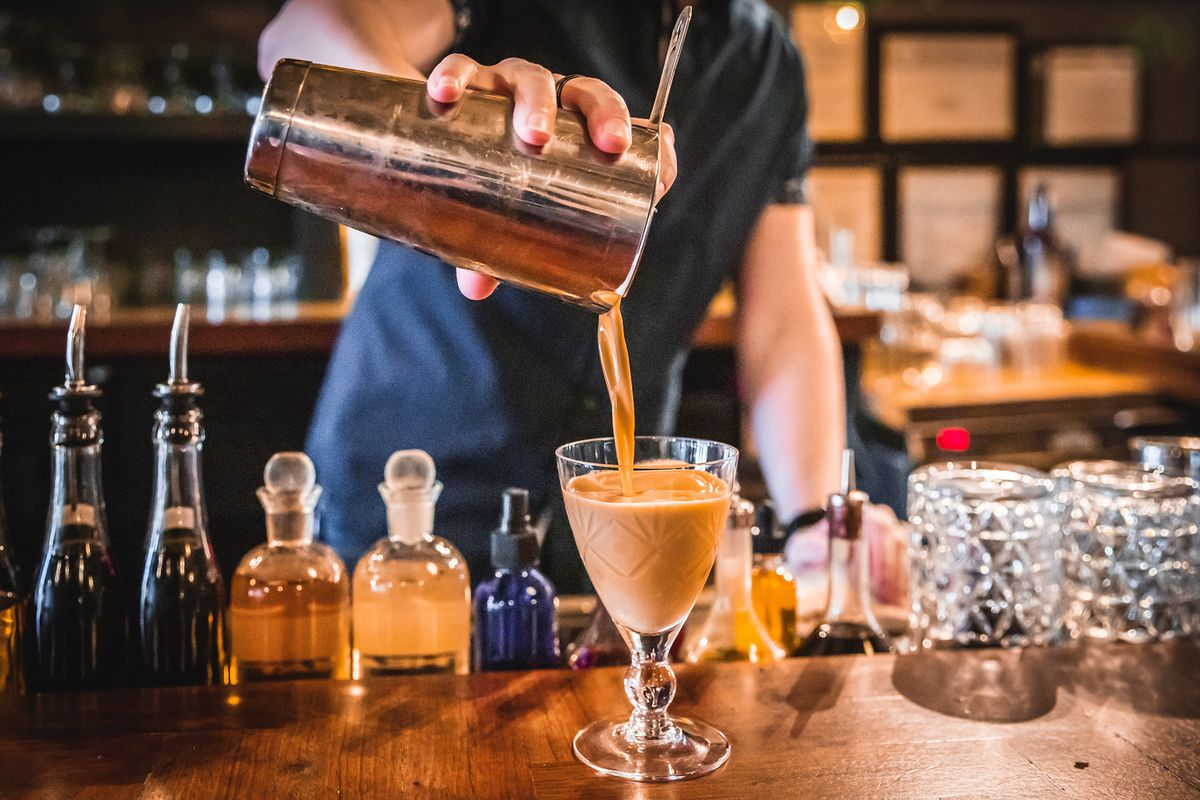 A hand pouring a cocktail shaker full of chocolatey goodness.