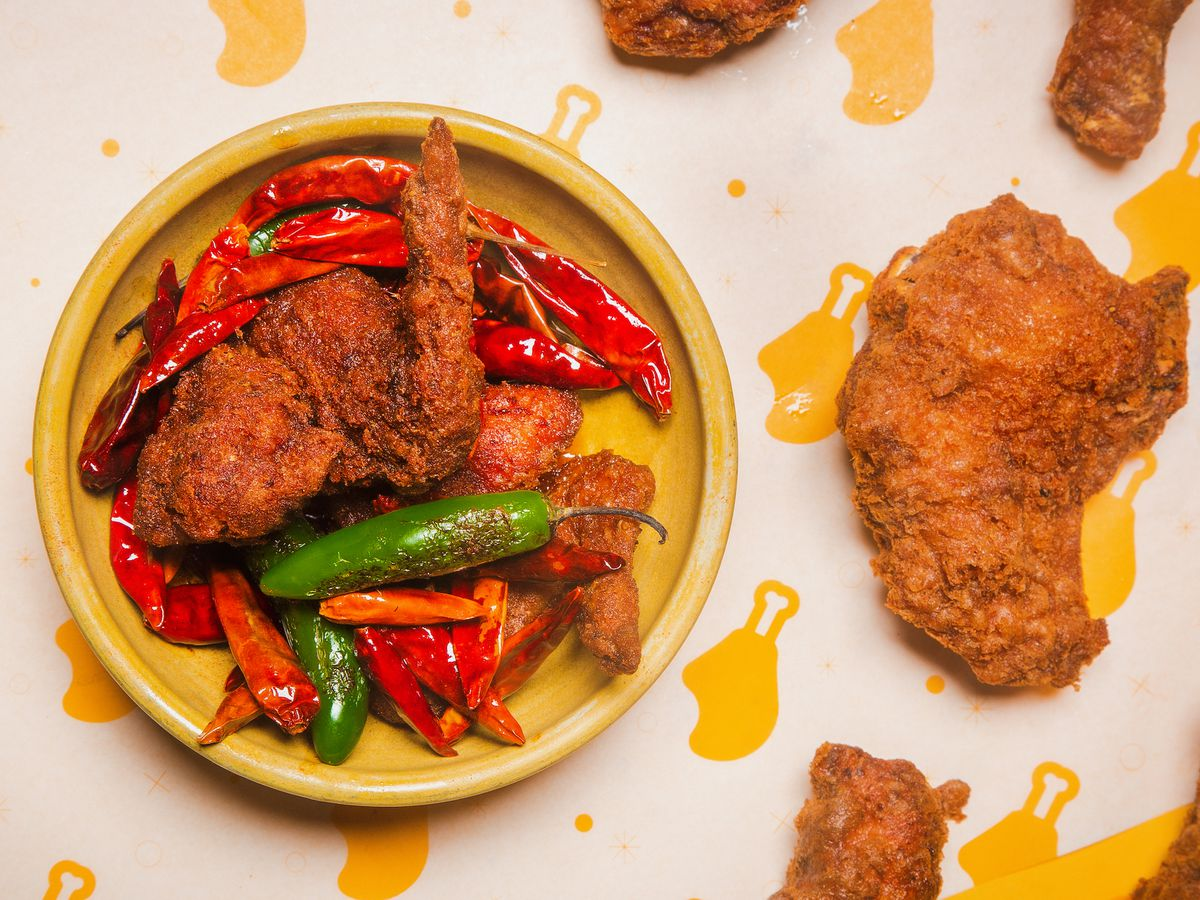 A yellow plate holds fried chicken wings and lots of spicy peppers.