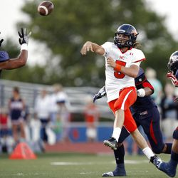 Mountain Crest's #5 Jamison Webb, center right, passes the ball over Woods Cross' #7 Junior Vailolo, left, during game action Friday, Aug. 31, 2012.