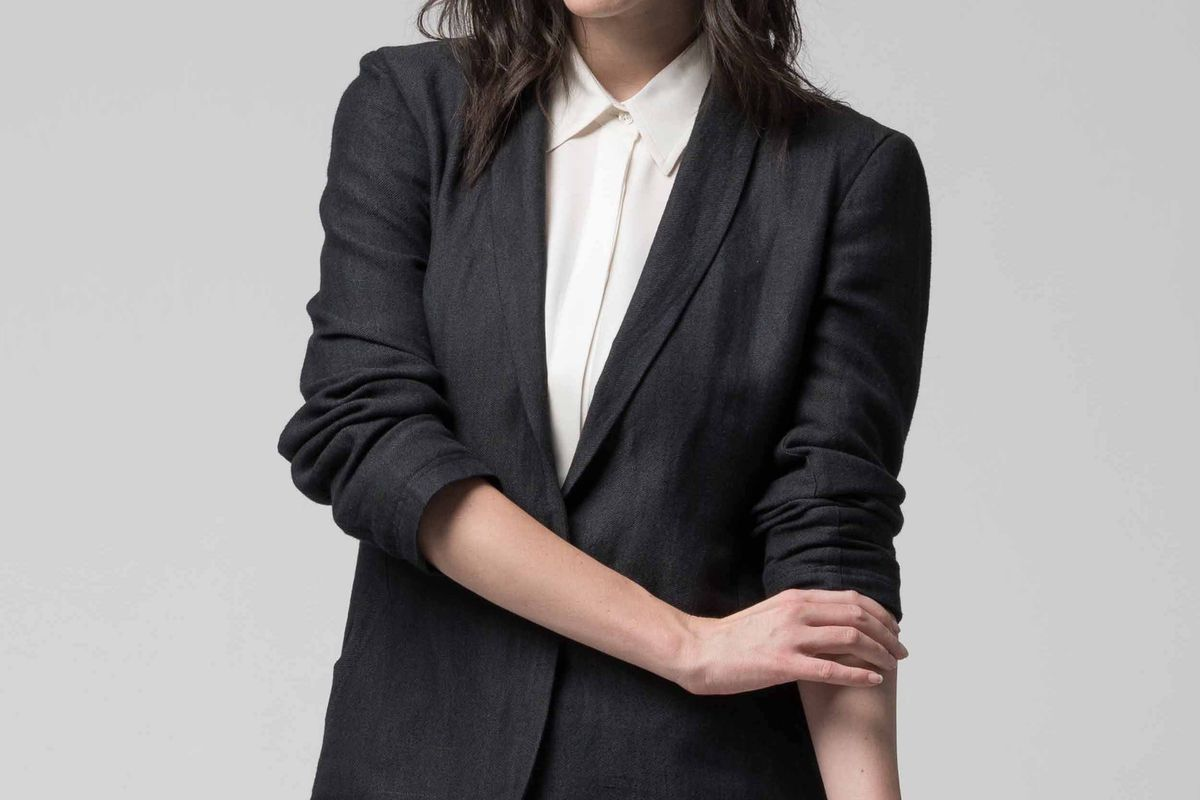 A woman wearing a dark charcoal suit jacket and pants, with a white blouse