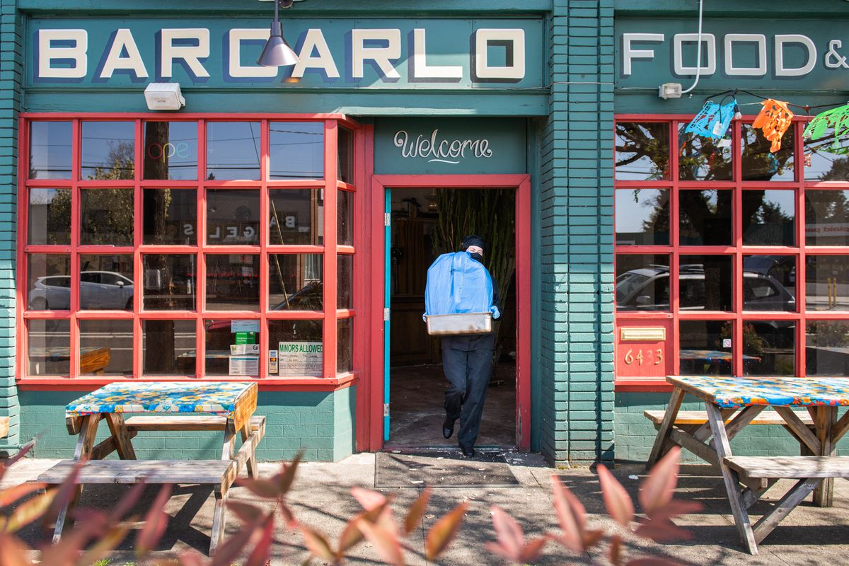 A woman in all black, a black face mask, and bright blue latex gloves carries a large, tall container of burritos out of her restaurant, Bar Carlo.