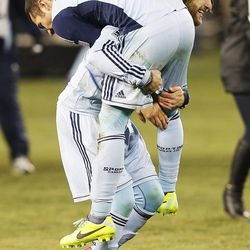 Kansas City's Graham Zusi picks up teammate Benny Feilhaber as they celebrate their win over Real Salt Lake Saturday, Dec. 7, 2013 in MLS Cup action.