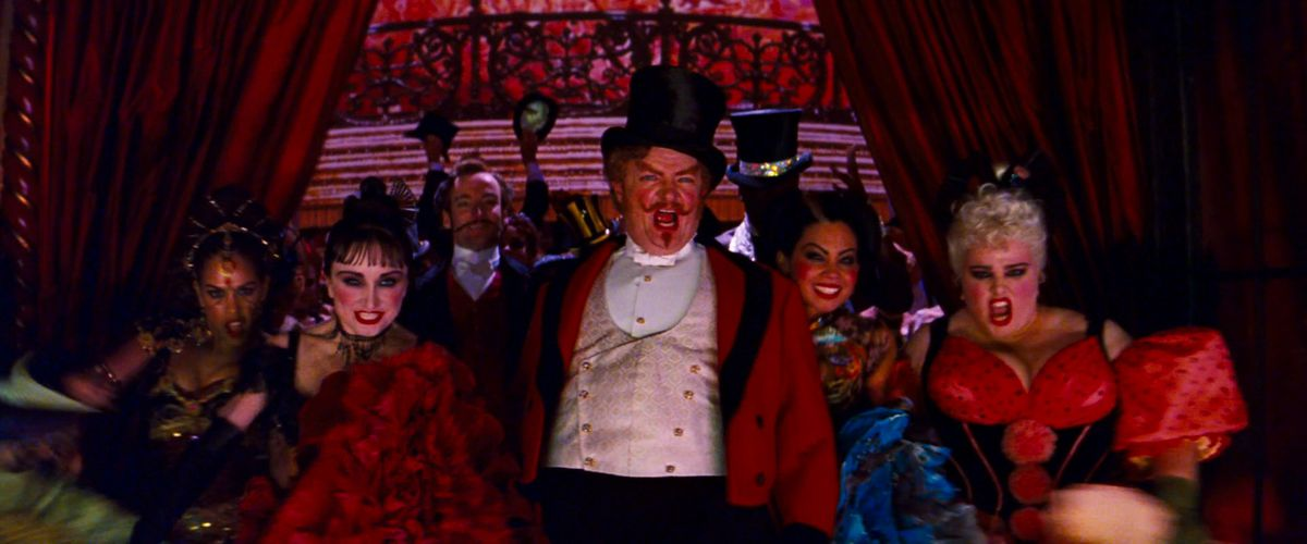 Jim Broadbent leads a chorus of chorus girls through the red curtains in Moulin Rouge