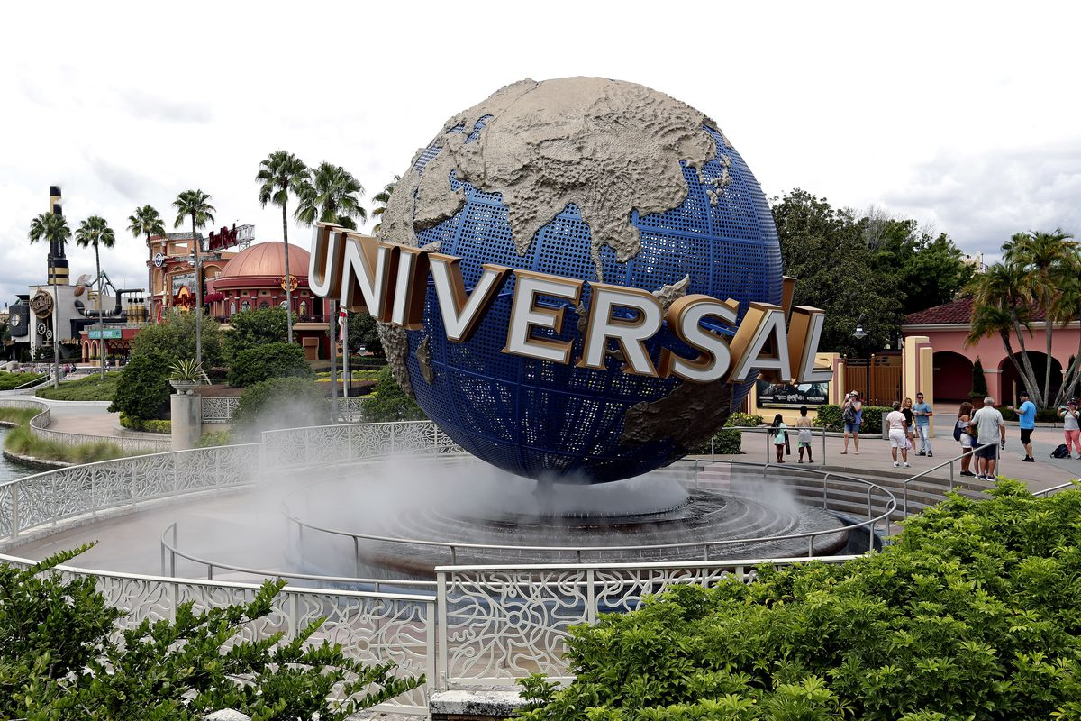 FILE - In this Aug. 5, 2019 file photo, guests cool off under a water mist by the globe at Universal Studios City Walk at Universal Studios Florida in Orlando, Fla. In the wake of the coronavirus crisis, the company that owns Universal theme parks around the world says it's delaying construction on a fourth theme park in Florida and that the opening of a Nintendo-themed park in Japan will be pushed back by a few months.